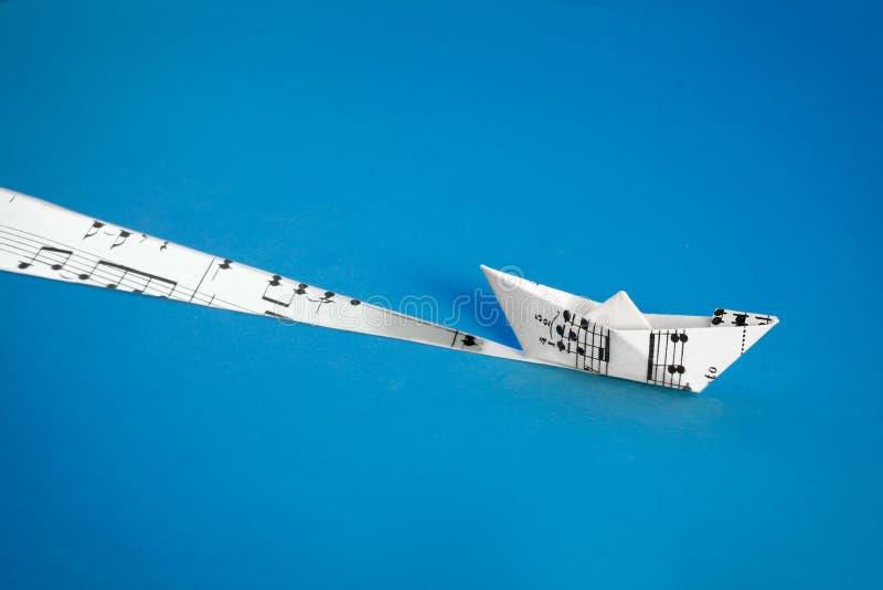 Βάρκα εγγράφου φιαγμένη από μουσικό φύλλο αποτελέσματος στο μπλε υπόβαθρο στοκ φωτογραφία