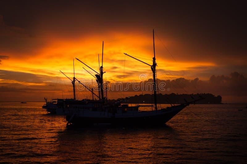 Βάρκα και ηλιοβασίλεμα Penisi σκιαγραφιών σε Sorong, δυτική Παπούα στοκ εικόνα