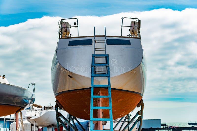 Βάρκα με τα σκαλοπάτια οπίσθια, προετοιμασμένος για την επισκευή στο σταθμό νερού στοκ φωτογραφία με δικαίωμα ελεύθερης χρήσης