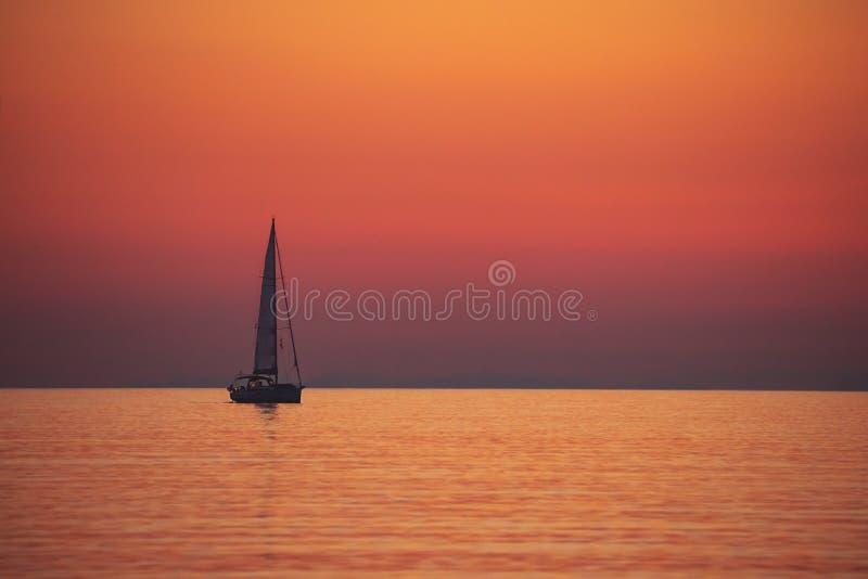 Βάρκα πανιών πέρα από το ηλιοβασίλεμα στοκ φωτογραφίες