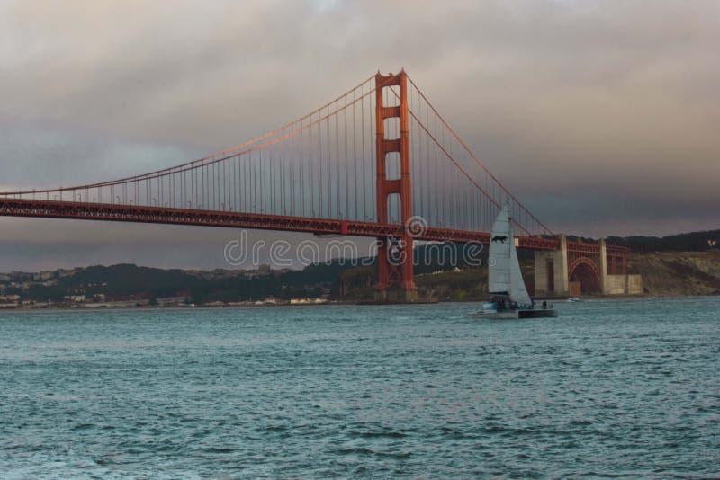 Βάρκα πανιών που περνά κάτω από τη διάσημη χρυσή γέφυρα πυλών στοκ εικόνα