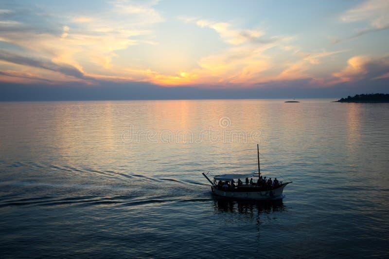 Βάρκα που πλέει στο ηλιοβασίλεμα στοκ φωτογραφίες