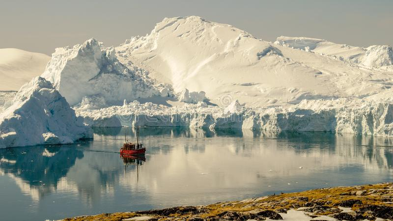 Βάρκα που ταξιδεύει μεταξύ των παγόβουνων στη Γροιλανδία στοκ φωτογραφίες