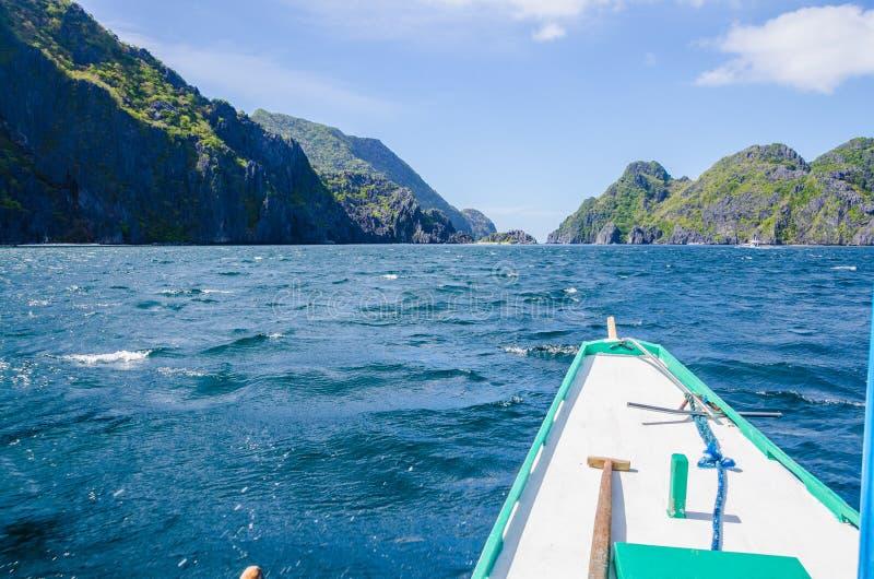 Βάρκα της Banca που πλησιάζει το νησί Mantiloc τη θυελλώδη ημέρα, EL, Nido, Palawan Φιλιππίνες στοκ φωτογραφία