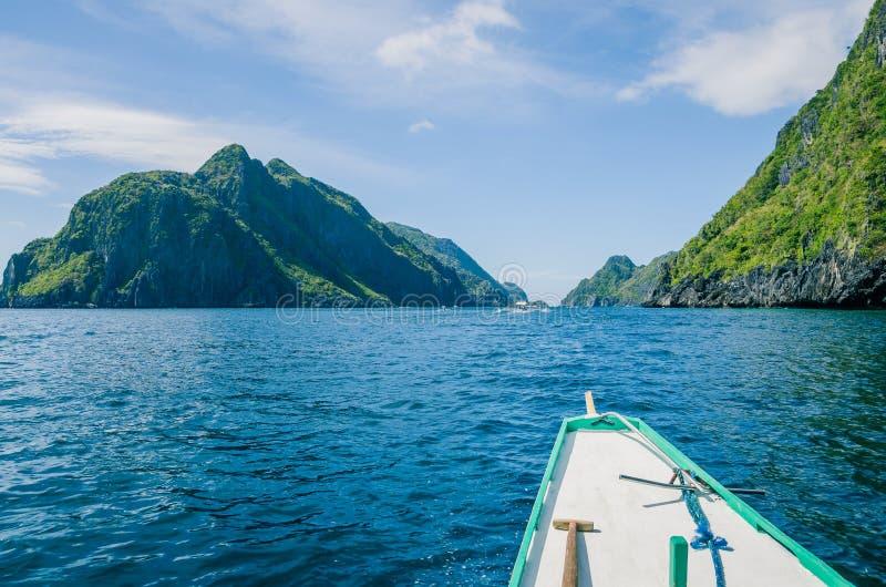 Βάρκα της Banca που πλησιάζει το νησί Mantiloc τη θυελλώδη ημέρα, EL, Nido, Palawan Φιλιππίνες στοκ εικόνα
