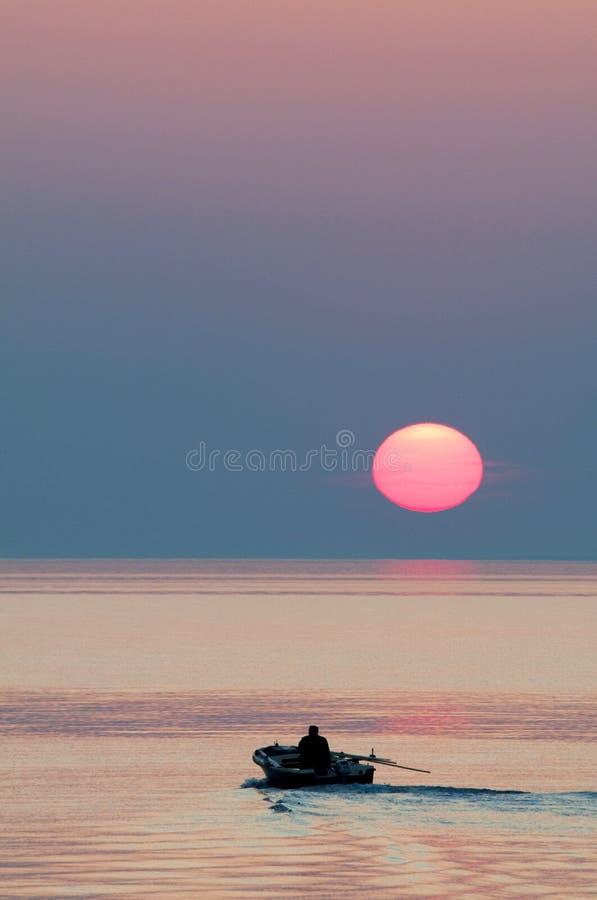 Βάρκα του Φίσερ στο ηλιοβασίλεμα στον ορίζοντα επάνω από τη θάλασσα στοκ εικόνες με δικαίωμα ελεύθερης χρήσης