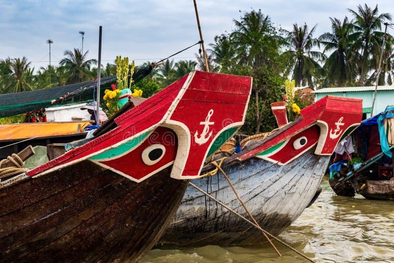 Βάρκες με τα μάτια και διακόσμηση ζωγραφικής αγκύρων στην πλώρη, που δένεται στα λασπώδη νερά του Mekong δέλτα, Βιετνάμ στοκ εικόνες