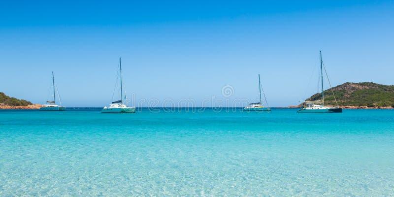 Βάρκες που δένουν στο τυρκουάζ νερό της παραλίας Rondinara στους πυρήνες στοκ εικόνες