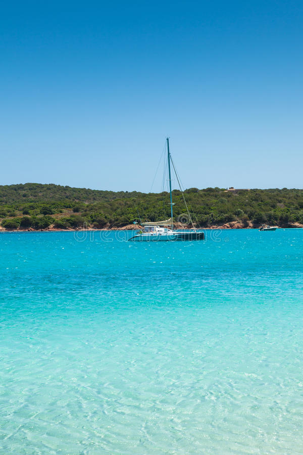 Βάρκες που δένουν στο τυρκουάζ νερό της παραλίας Rondinara στους πυρήνες στοκ εικόνα