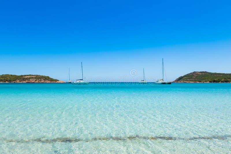 Βάρκες που δένουν στο τυρκουάζ νερό της παραλίας Rondinara στους πυρήνες στοκ φωτογραφίες