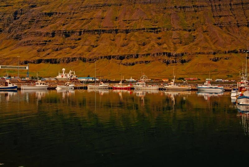 Βάρκες που ελλιμενίζονται στη θάλασσα στο τοπίο βουνών σε Sejdisfjordur, Ισλανδία Εν πλω ακτή τεχνών νερού που ταξιδεύει από το ν στοκ εικόνες