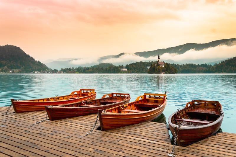 Βάρκες στην αιμορραγημένη λίμνη στη Σλοβενία Λίμνη βουνών με το μικρό νησί, την εκκλησία και το ζωηρόχρωμο ουρανό, τυποποιημένη α στοκ φωτογραφία με δικαίωμα ελεύθερης χρήσης