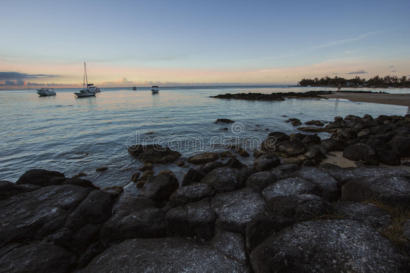 Βάρκες στη θάλασσα στην ανατολή στοκ εικόνες
