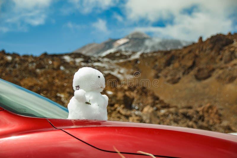 Βάση του ηφαιστείου Teide Χιονάνθρωπος επάνω στην κουκούλα του κόκκινου αυτοκινήτου Peack Teide με τα άσπρα σημεία χιονιού, που κ στοκ φωτογραφία με δικαίωμα ελεύθερης χρήσης