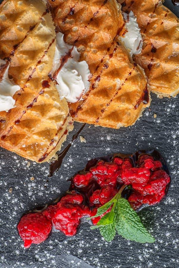 Βάφλα του Βελγίου με τη μορφή καρδιών που ολοκληρώνεται με το κάλυμμα σοκολάτας, την κτυπημένη κρέμα και τα φρέσκα σμέουρα στην κ στοκ φωτογραφίες