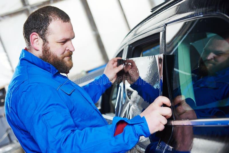 Βάψιμο αυτοκινήτων Αυτοκινητικός μηχανικός τεχνικός που εφαρμόζει το φύλλο αλουμινίου στοκ φωτογραφία