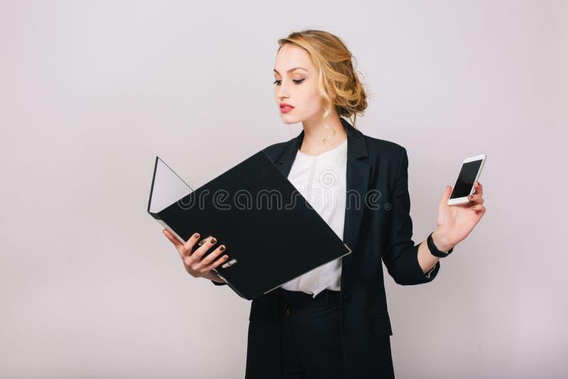 Βέβαια αρκετά ξανθή επιχειρηματίας στο κοστούμι γραφείων που εξετάζει το φάκελλο στα χέρια, που κρατούν το τηλέφωνο στο άσπρο υπό στοκ φωτογραφία με δικαίωμα ελεύθερης χρήσης
