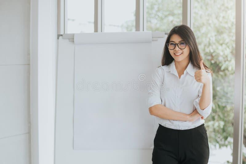 Βέβαια ασιατική γυναίκα με το κενό flipchart στοκ εικόνες