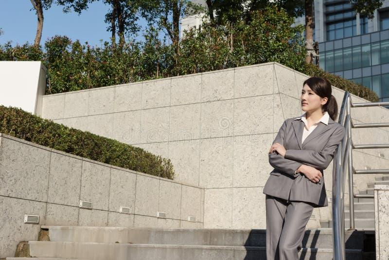 Βέβαια ασιατική επιχειρησιακή γυναίκα που στέκεται μέσα έξω από το γραφείο μέσα στοκ εικόνα