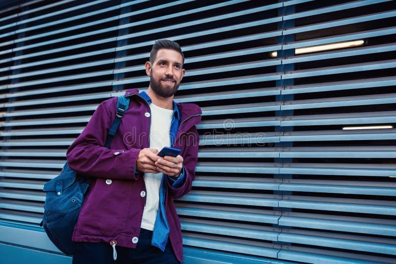 Βέβαια γενειοφόρος εκμετάλλευση ατόμων μέσα και κινητό τηλέφωνο στεμένος κοντά στον τοίχο οδών το ηλιόλουστο θερινό βράδυ στοκ εικόνα με δικαίωμα ελεύθερης χρήσης