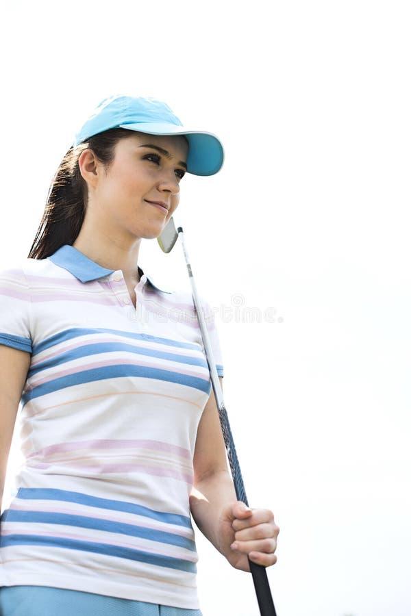 Βέβαια γυναίκα που κοιτάζει μακριά κρατώντας το γκολφ κλαμπ ενάντια στο σαφή ουρανό στοκ εικόνα
