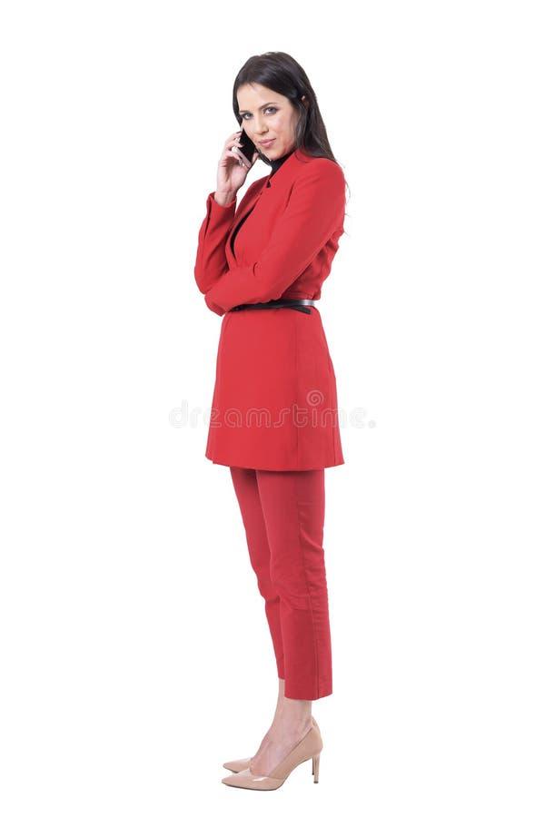 Βέβαια επιτυχής επιχειρησιακή γυναίκα που μιλά στο κινητό τηλέφωνο που γυρίζει και που εξετάζει τη κάμερα στοκ φωτογραφία