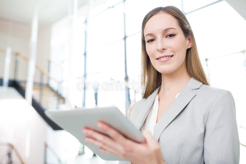 Βέβαια επιχειρηματίας που χαμογελά ενώ υπολογιστής ταμπλετών εκμετάλλευσης στοκ εικόνες