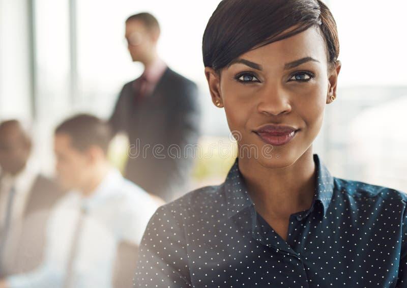 Βέβαια επιχειρησιακή γυναίκα στην αρχή με την ομάδα στοκ φωτογραφία