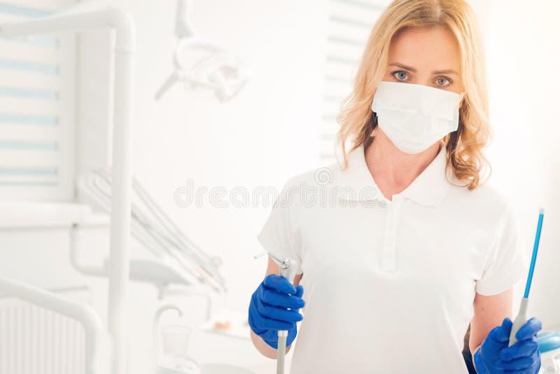 Βέβαια θηλυκή τοποθέτηση οδοντιάτρων με τα εργαλεία για την επεξεργασία δοντιών στοκ εικόνα με δικαίωμα ελεύθερης χρήσης