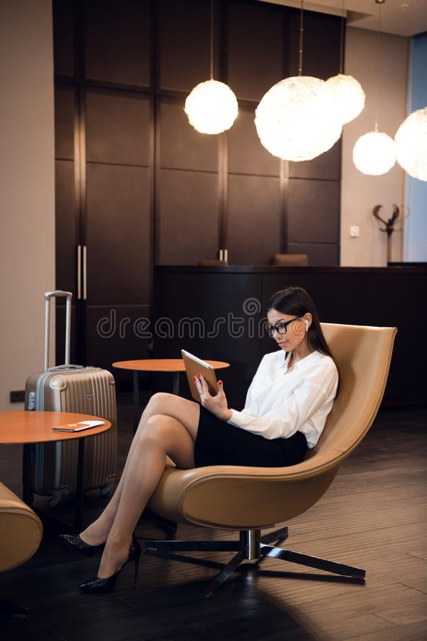 Βέβαια μουσική ακούσματος επιχειρηματιών στον υπολογιστή ταμπλετών της καθμένος στην καρέκλα στο επιχειρησιακό σαλόνι αερολιμένων στοκ φωτογραφία με δικαίωμα ελεύθερης χρήσης