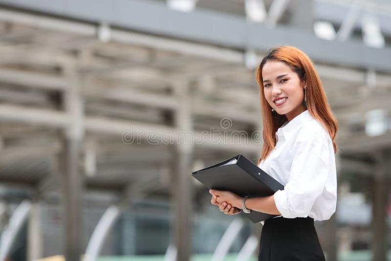 Βέβαια νέα ασιατική επιχειρησιακή γυναίκα με το σύνδεσμο δαχτυλιδιών που στέκεται στο εξωτερικό γραφείο στοκ εικόνες με δικαίωμα ελεύθερης χρήσης