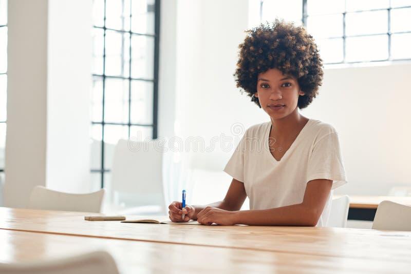 Βέβαια νέα αφρικανική γυναίκα σπουδαστής που μελετά σε έναν πίνακα πανεπιστημιουπόλεων στοκ φωτογραφίες με δικαίωμα ελεύθερης χρήσης
