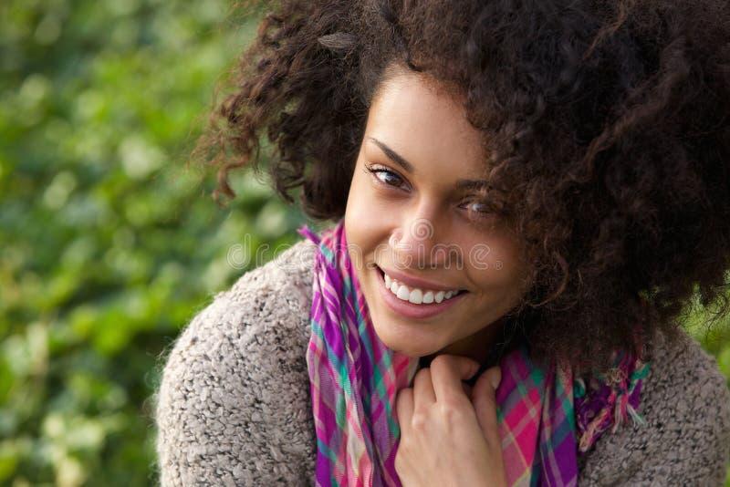 Βέβαια νέα γυναίκα που χαμογελά υπαίθρια στοκ φωτογραφία
