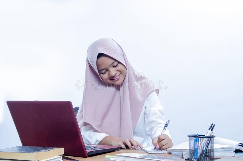 Βέβαια νέα γυναίκα χαμόγελου που εργάζεται στο γραφείο της στοκ φωτογραφίες