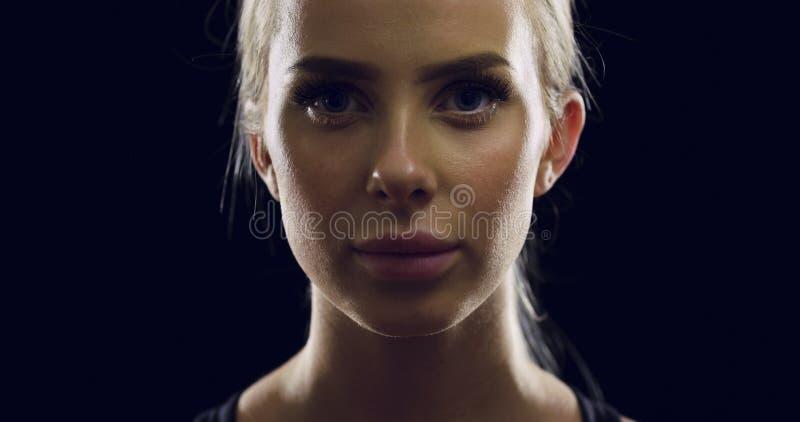 Βέβαια νέα ξανθή γυναίκα στο μαύρο στούντιο στοκ εικόνα