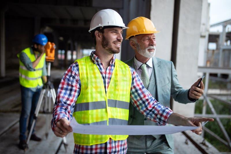 Βέβαια ομάδα των αρχιτεκτόνων και των μηχανικών που εργάζονται μαζί στο εργοτάξιο οικοδομής στοκ εικόνα