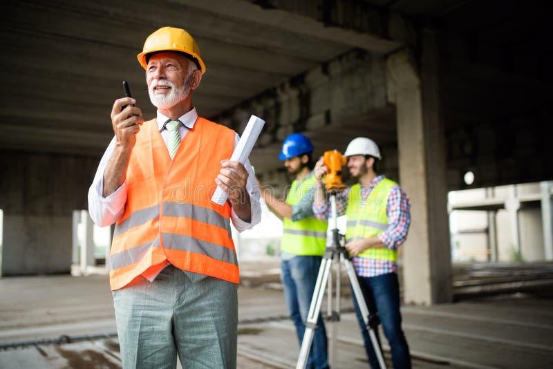 Βέβαια ομάδα των αρχιτεκτόνων και των μηχανικών που εργάζονται μαζί στο εργοτάξιο οικοδομής στοκ φωτογραφίες