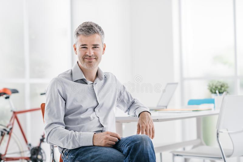 Βέβαια σύγχρονη συνεδρίαση επιχειρηματιών στο γραφείο του και χαμόγελο στη κάμερα στοκ φωτογραφία με δικαίωμα ελεύθερης χρήσης