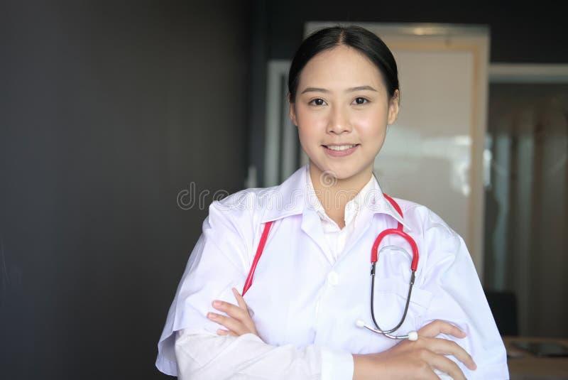 Βέβαια τοποθέτηση γιατρών χαμόγελου νέα θηλυκή με τα όπλα που διασχίζονται στοκ εικόνα