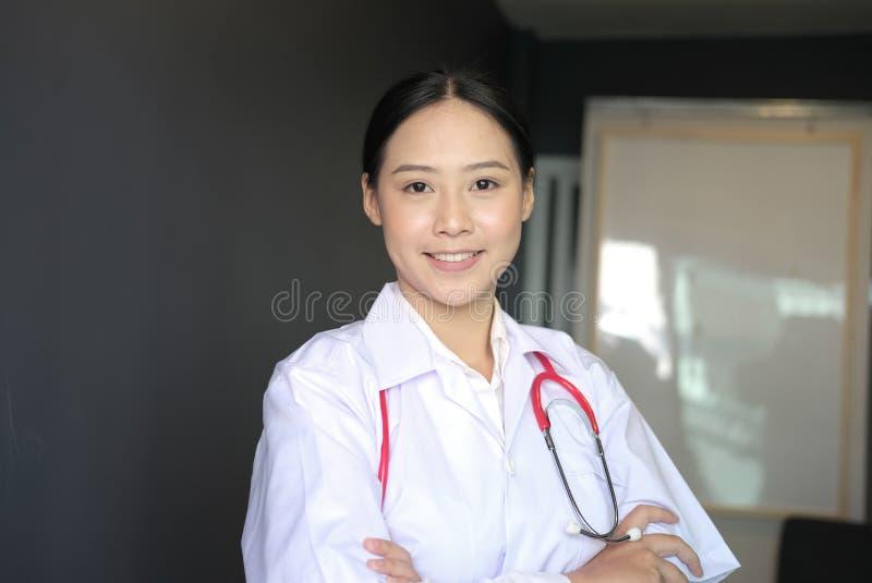 Βέβαια τοποθέτηση γιατρών χαμόγελου νέα θηλυκή με τα όπλα που διασχίζονται στοκ εικόνα με δικαίωμα ελεύθερης χρήσης