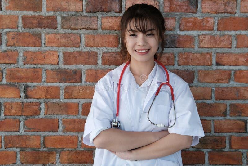 Βέβαια τοποθέτηση γιατρών χαμόγελου νέα θηλυκή με τα όπλα που διασχίζονται στοκ εικόνες