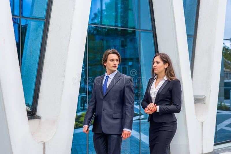 Βέβαια businesspersons που μιλούν μπροστά από το σύγχρονο κτίριο γραφείων Οι επιχειρηματίες και η επιχειρηματίας έχουν την επιχεί στοκ εικόνα με δικαίωμα ελεύθερης χρήσης