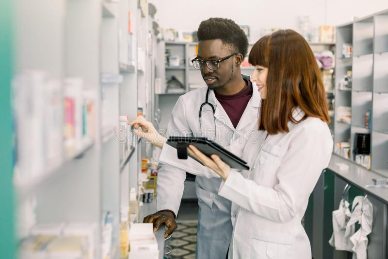 Βέβαιοι αρσενικοί και θηλυκοί φαρμακοποιοί στο φαρμακείο θηλυκός φαρμακοποιός που μιλά με το συνάδελφό της για τις ιδιότητες και στοκ εικόνες με δικαίωμα ελεύθερης χρήσης