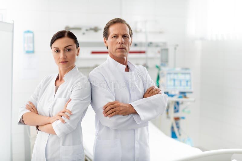 Βέβαιοι ιατρικοί εργαζόμενοι με τα διασχισμένα όπλα που θέτουν στο δωμάτιο νοσοκομείων στοκ εικόνες
