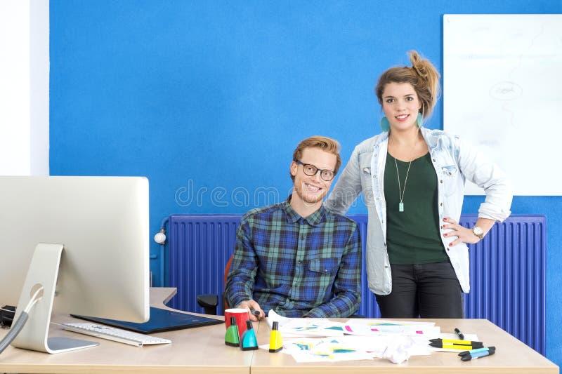 Βέβαιοι σχεδιαστές στο δημιουργικό γραφείο στοκ εικόνες