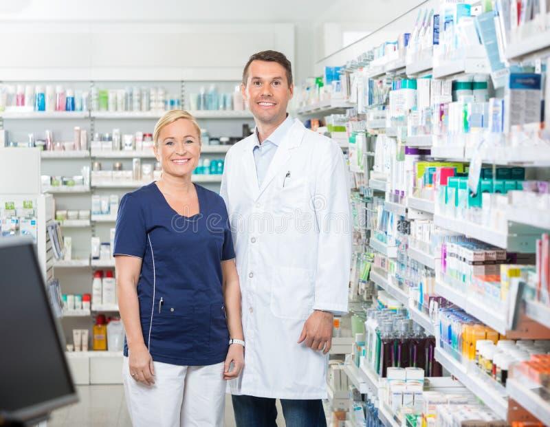 Βέβαιοι φαρμακοποιός και βοηθός που στέκονται μέσα στοκ εικόνες
