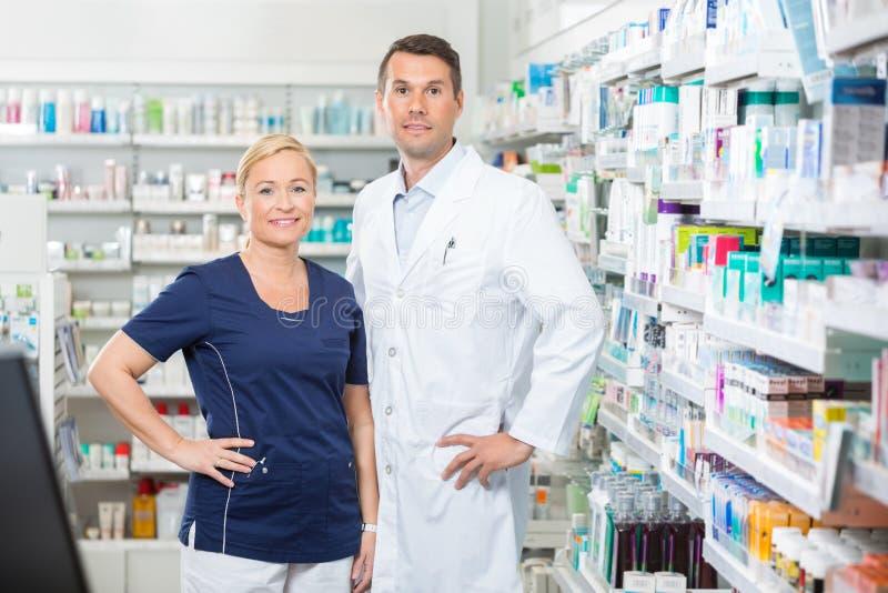 Βέβαιοι φαρμακοποιός και βοηθός που στέκονται με τα χέρια στο ισχίο στοκ φωτογραφία με δικαίωμα ελεύθερης χρήσης