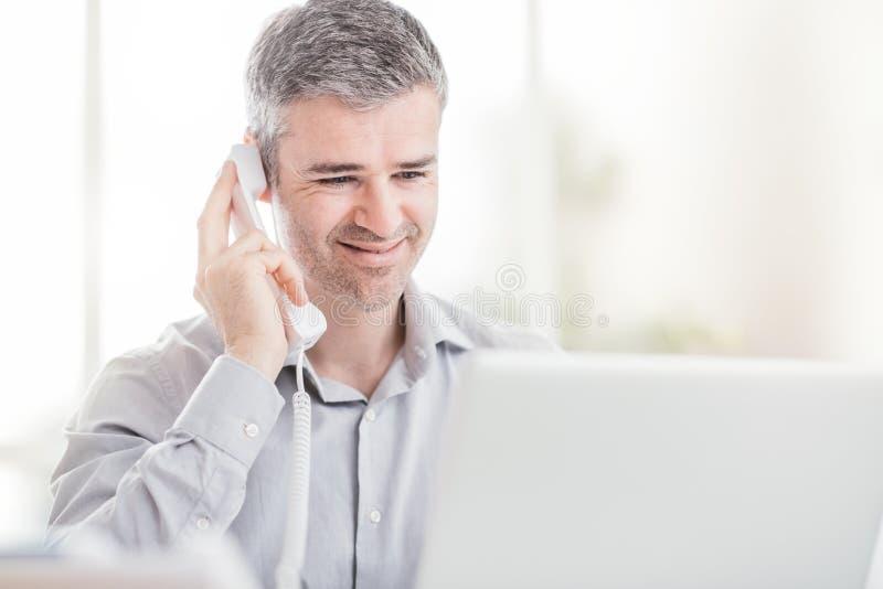 Βέβαιοι χαμογελώντας επιχειρηματίας και σύμβουλος που εργάζονται στο γραφείο του, έχει ένα τηλεφώνημα στοκ εικόνες