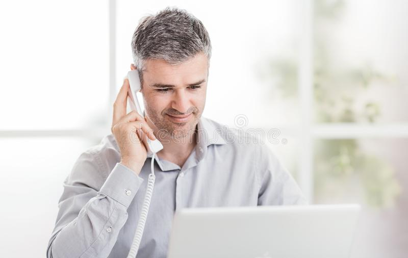 Βέβαιοι χαμογελώντας επιχειρηματίας και σύμβουλος που εργάζονται στο γραφείο του, έχει: έννοια επικοινωνίας και επιχειρήσεων στοκ φωτογραφίες