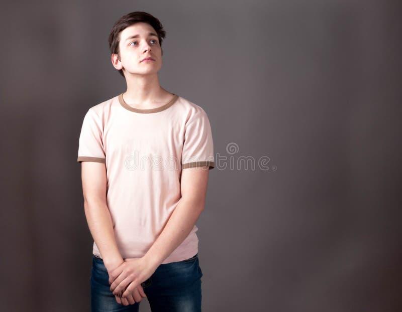 Βέβαιος έφηβος στην μπεζ μπλούζα στοκ εικόνες